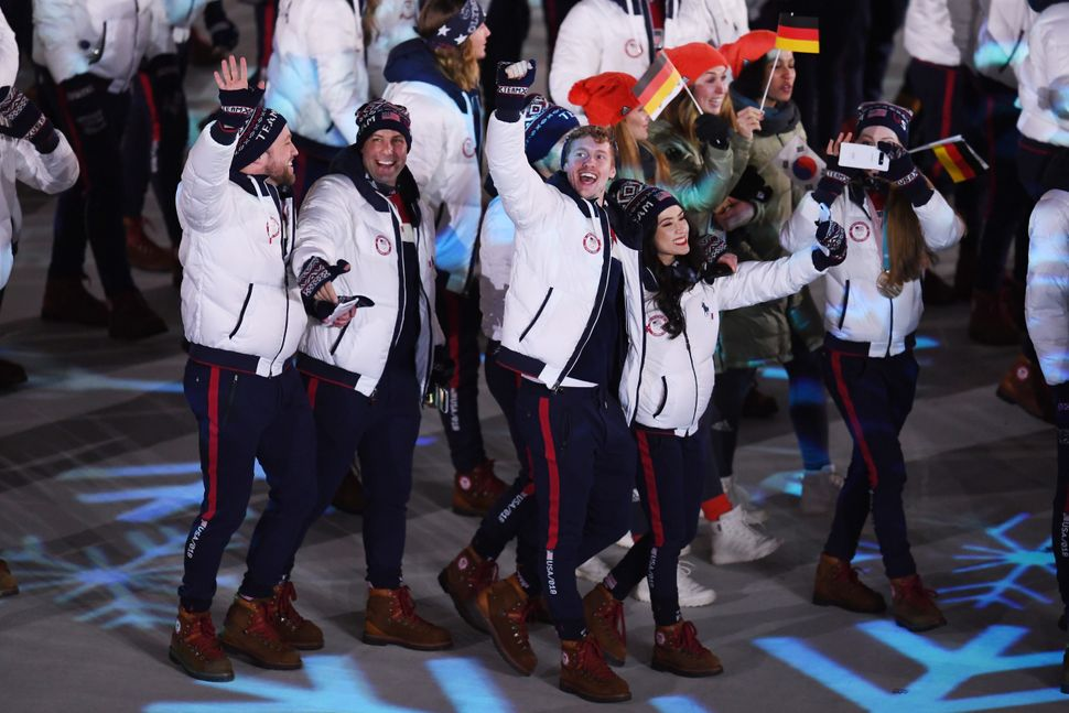 Madison Chock and Evan Bates of the United States walk with Team USA in the Parade of Athletes.