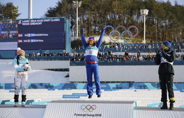 Gold medallist Marit Bjoergen of Norway is seen flanked by silver medallist Krista Parmakoski of Finland and bronze medallist