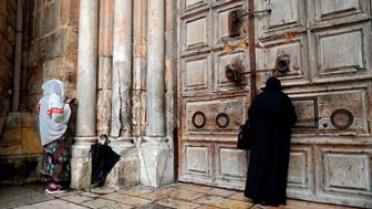 TOPSHOT - Two Christian women pray by the closed door of the main entrance of the Church of the Holy Sepulchre in the Old City of Jerusalem on February 26, 2018 after Christian leaders took the rare step of closing the church, seen as the holiest site in Christianity, the previous day at noon.  Jerusalem's Church of the Holy Sepulchre, built at the site where Christians believe Jesus was buried, remained closed today in protest at Israeli tax measures and a proposed property law.  / AFP PHOTO / THOMAS COEX        (Photo credit should read THOMAS COEX/AFP/Getty Images)