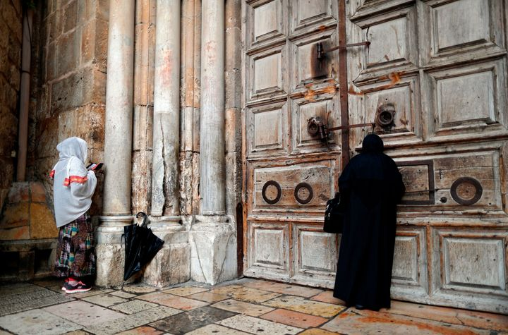 Two Christian women pray by the closed door of the main entrance of the Church of the Holy Sepulchre in the Old City of Jerus