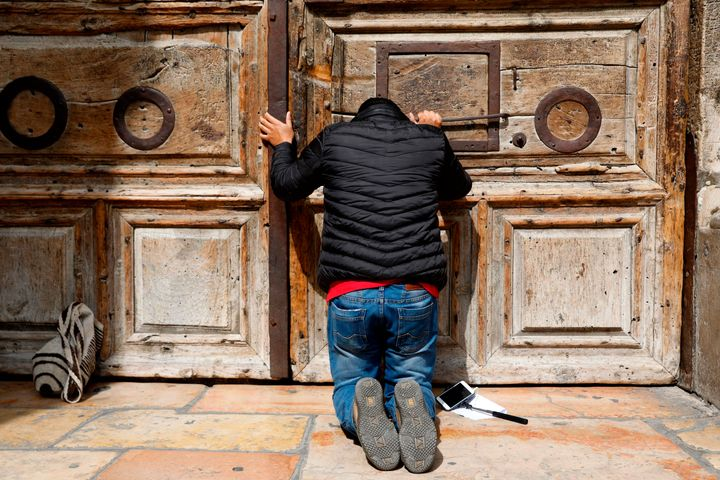A pilgrim prays outside the closed gate of the Church of the Holy Sepulchre in Jerusalem's Old City on February 25, 201