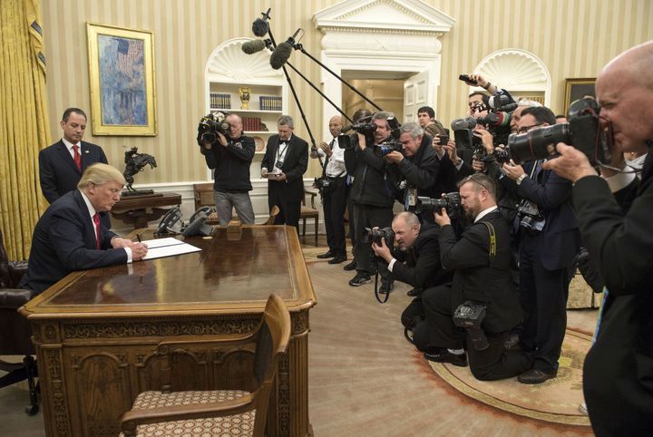 President Donald Trump signs an executive order on Jan. 20, 2017, that commands federal agencies to try to waive or delay requirements of the Affordable Care Act.