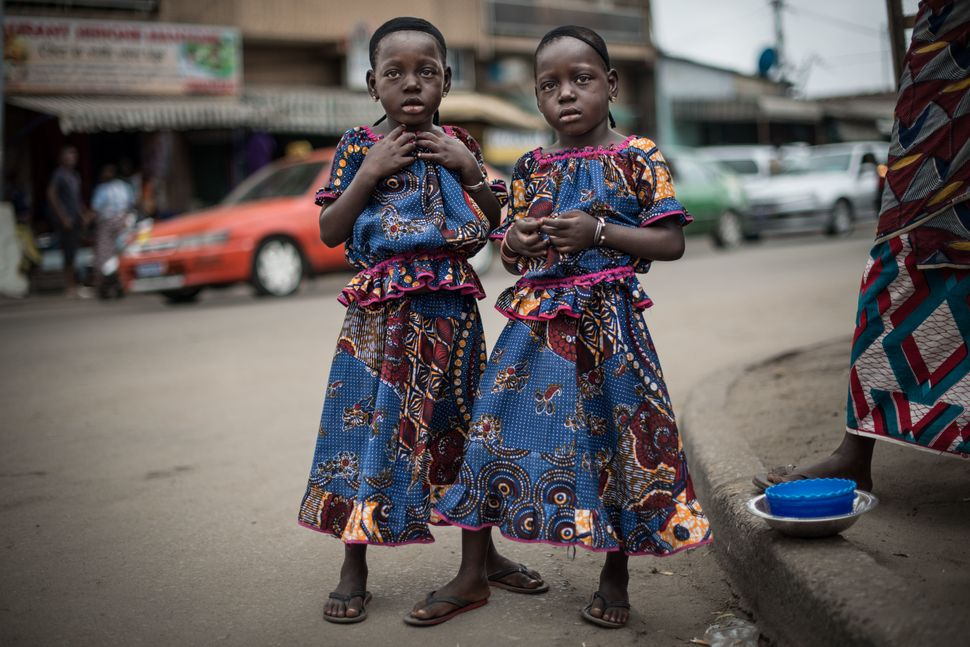 Rasidatou and Latifatou, 4, pose for a portrait on a street in the Koumassi district of Abidjan, Ivory Coast, on July 25, 201