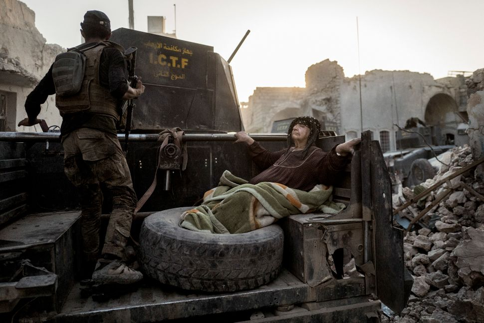 An elderly woman is driven through the city on the back of one of Golden Division's Humvees. The temperature is nearly