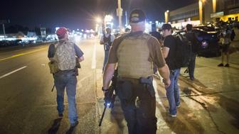FERGUSON, MO - AUGUST 10:  Oath Keepers, carrying rifles, walk along West Florrisant Street as  demonstrators, marking the first anniversary of the shooting of Michael Brown, protest on August 10, 2015 in Ferguson, Missouri. Brown was shot and killed by a Ferguson police officer on August 9, 2014. His death sparked months of sometimes violent protests in Ferguson and drew nationwide focus on police treatment of black suspects.  (Photo by Scott Olson/Getty Images)