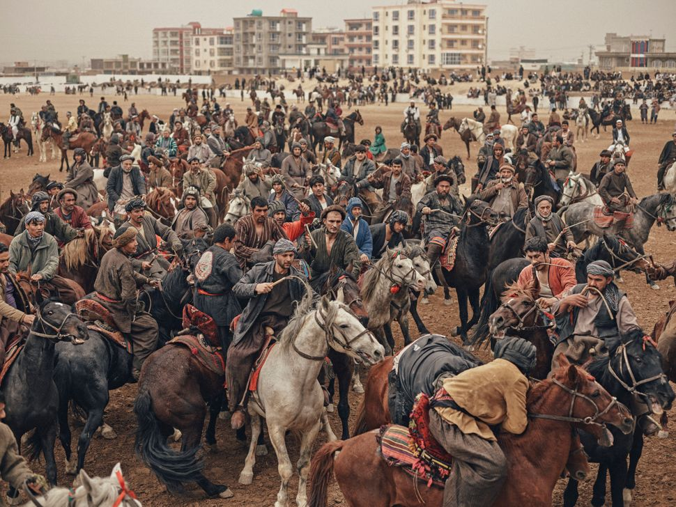 Horsemen fight for a headless calf carcass during a buzkashi match on the day of Nawroz, or Persian New Year, in Mazar-e Shar
