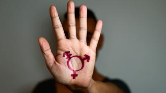 closeup of a transgender symbol painted in the palm of the hand of a young caucasian person