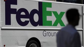 SAN FRANCISCO, CA - JUNE 21:  A pedestrian walks by a FedEx delivery truck on June 21, 2016 in San Francisco, California. FedEx Corp. is will announce its fourth-quarter earnings today after the closing bell.  (Photo by Justin Sullivan/Getty Images)