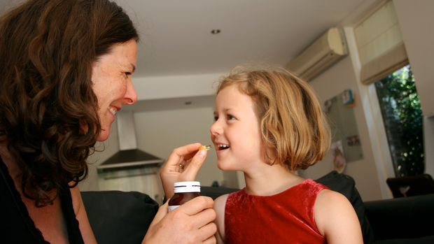 young girl being given childrens supplements or vitamins by her mother