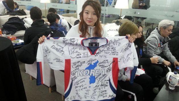 남북 아이스하키 단일팀 선수들 35명이 사인한 단일팀 유니폼을 대표팀의 고혜인 선수가 들고