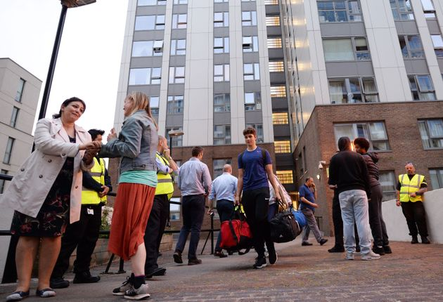 Residents leave the Taplow tower block on the Chalcots Estate in Camden, London, as the building is evacuated...