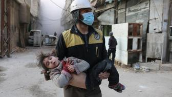 DAMASCUS, SYRIA - FEBRUARY 23: (EDITORS NOTE: Image contains graphic content) Civil defense team member carries a wounded baby rescued from a wreckage after Assad regime forces carried out airstrikes over the de-escalation zone in Arbin town of Eastern Ghouta in Damascus, Syria on February 23, 2018. (Photo by Qusay Noor/Anadolu Agency/Getty Images)
