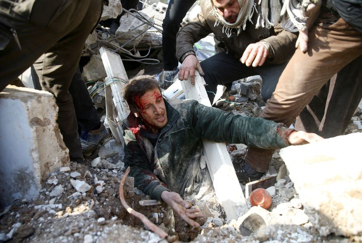 A manis stuck under debris after an airstrikein the eastern Damascus suburb of Ghouta, Syria, on Jan. 9, 2018.