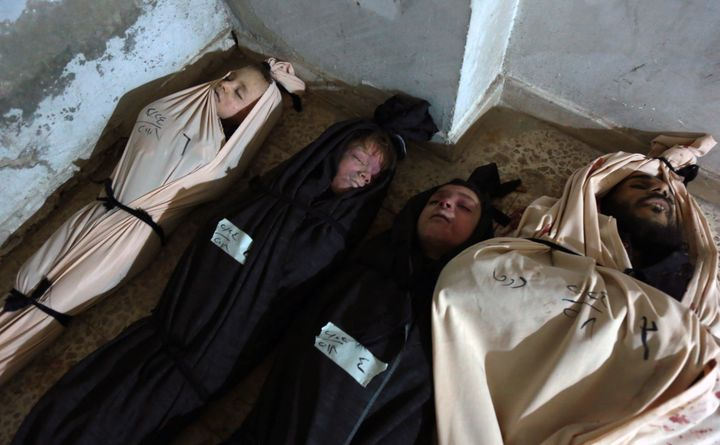 Bodies of civilians killed during reported regime bombardmentin eastern Ghoutaare shrouded and preparedfor