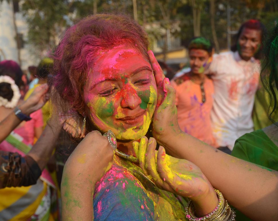Indian students smear on another with colored powder during the event of Holi celebration at Rabindra Bharati University in K