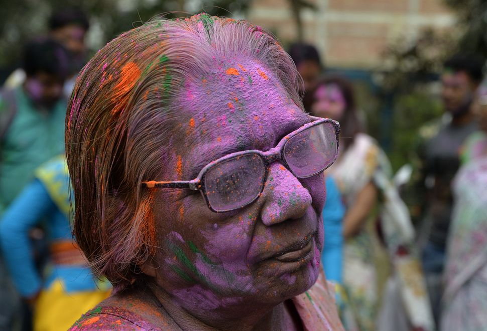 An Indian woman looks on after being covered with colored powder to celebrate the Hindu festival of Holi in Siliguri on Feb.