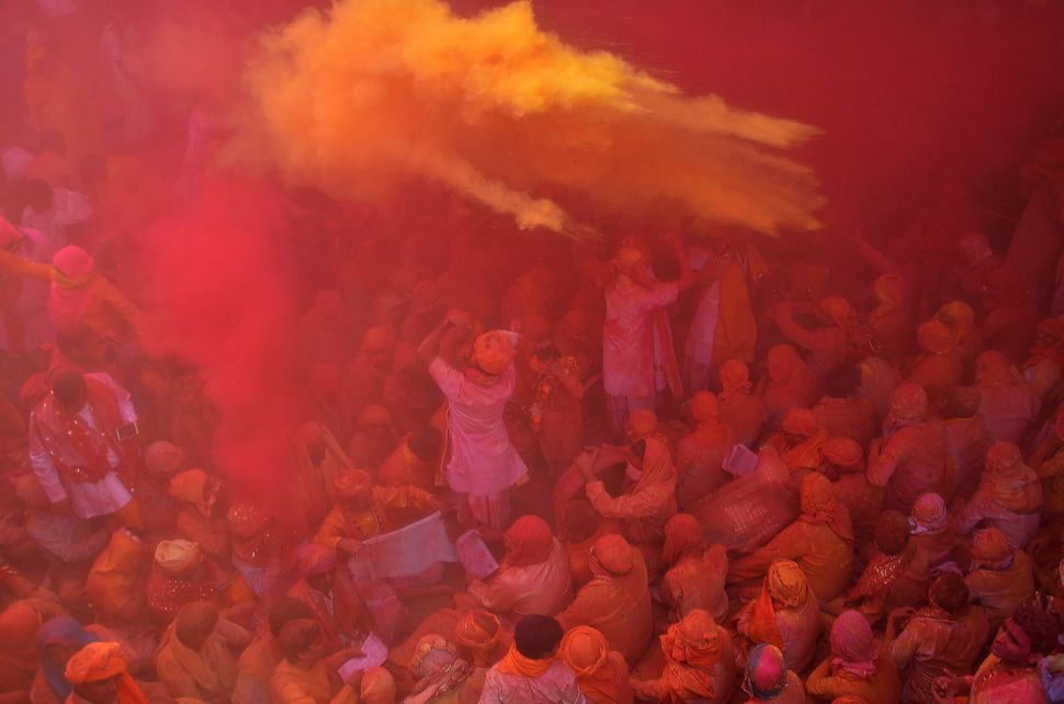 Indian Hindu devotees throw colored powder during the celebration of Holi at Sriji temple in Barsana in the northern Indian s