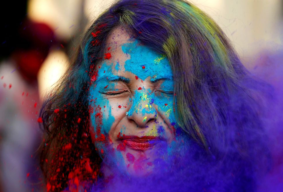 A student of Rabindra Bharati University reacts as fellow students throw colored powder in her face during the Holi celebrati
