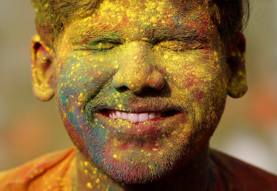 A student of Rabindra Bharati University, with his face smeared in colored powder, reacts in Kolkata, India.