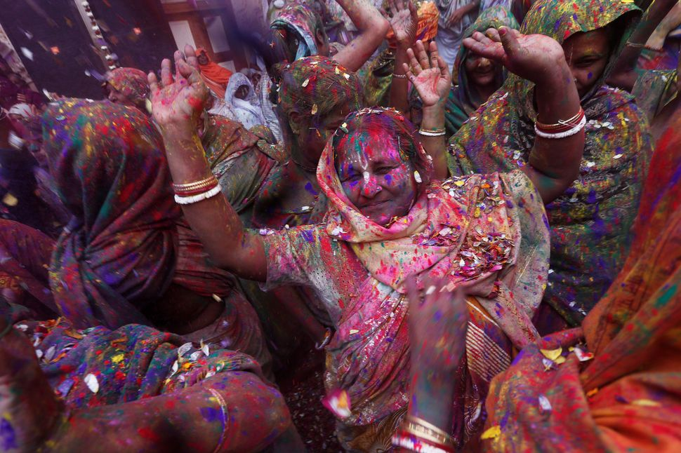 Widows daubed in colors dance as they take part in Holi celebrations in the town of Vrindavan in the northern state of Uttar