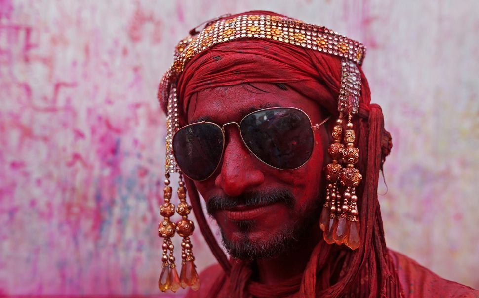 A Hindu devotee takes part in the religious festival of Holi inside a temple in Nandgaon village, in the state of Uttar Prade