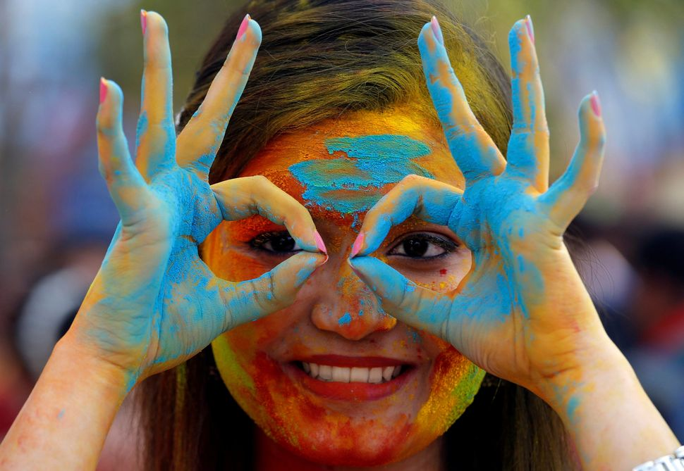 A student of Rabindra Bharati University, with her face smeared in colored powder, poses during celebrations for Holi inside