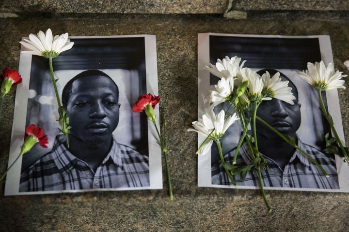 Flowers rest on top of pictures of Kalief Browder in New York on June 11, 2015.