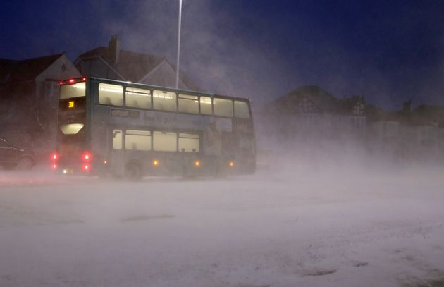 A bus passes through a snow storm in Whitley Bay as heavy snow has caused more misery for travellers