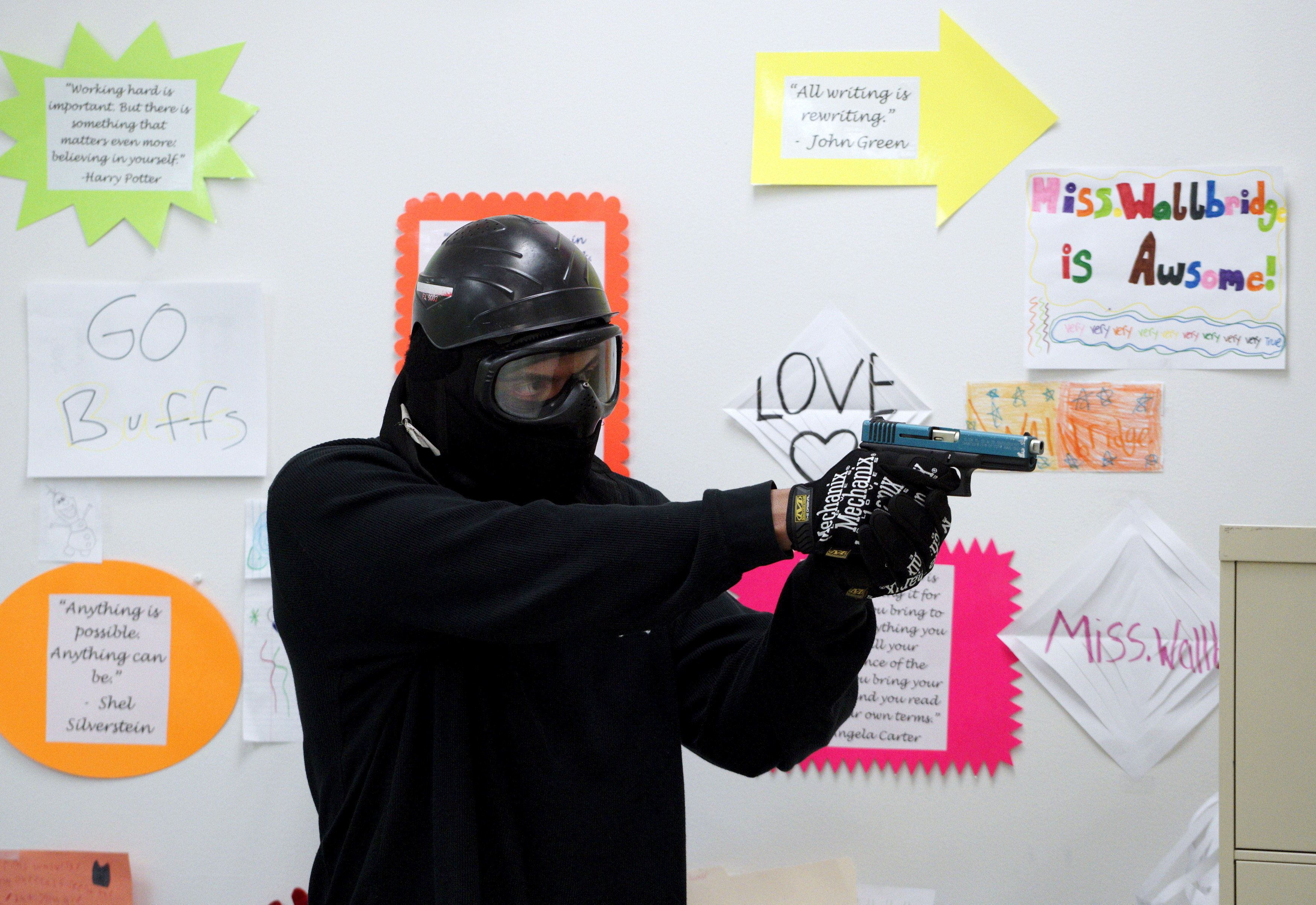"A student prepares to confront a ""gunman"" in a middle school classroom during an Active Shooter Response course offered by TAC ONE Consulting in Denver April 2, 2016. According to TAC ONE, the course, which is offered for the first time to concealed weapons permit carrying civilians, is designed at preparing people to effectively save lives prior to the arrival of law enforcement at an active shooter incident. REUTERS/Rick Wilking"