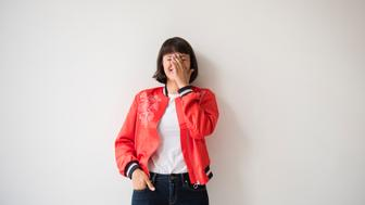 Laughing Hispanic woman wearing red jacket leaning on wall