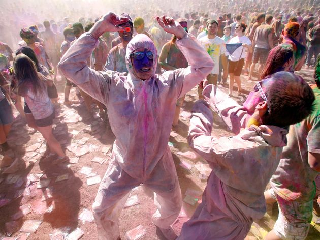 Participants dance and throw colored chalk during the Holi Festival of Colors at the Sri Sri Radha Krishna...
