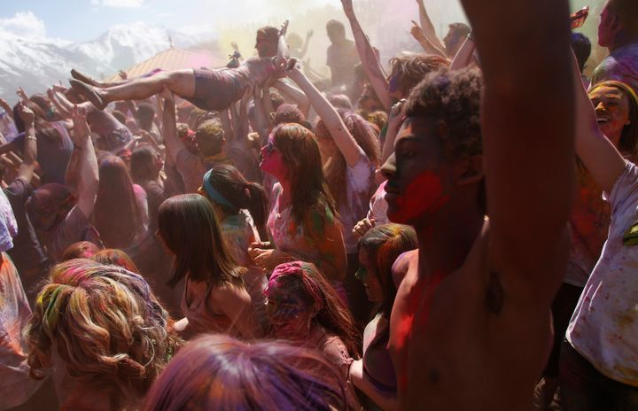Participants crowd surf, dance and throw colored chalk during the Holi Festival of Colors at the Sri Sri Radha Krishna