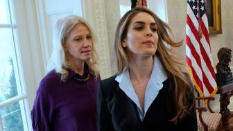 White House Communications Director Hope Hicks (C) departs as she and White House counselor Kellyanne Conway (L) stand on the sidelines while U.S. President Donald Trump speaks to reporters in the Oval Office at the White House in Washington, U.S. February 9, 2018.  REUTERS/Jonathan Ernst