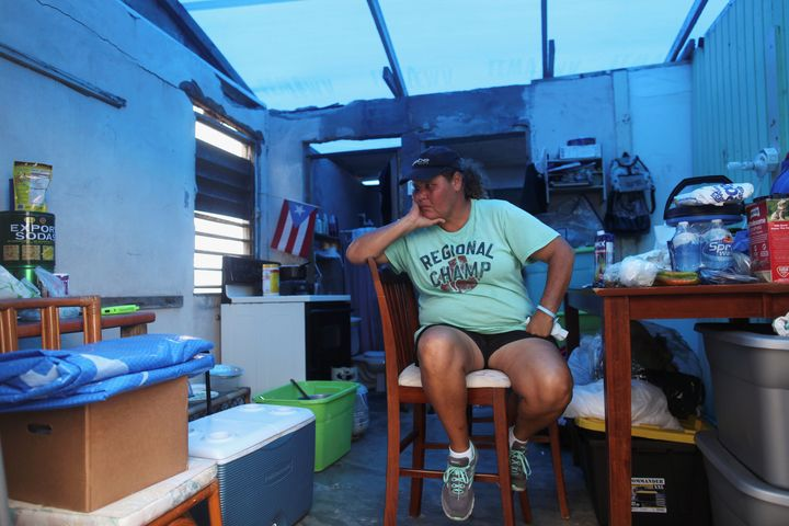 Jazmin Morales sits in her kitchen on Jan. 29 without power and with a plastic sheet replacing the roof in Yabucoa, Puer