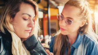 Young woman comforting sad friend at restaurant
