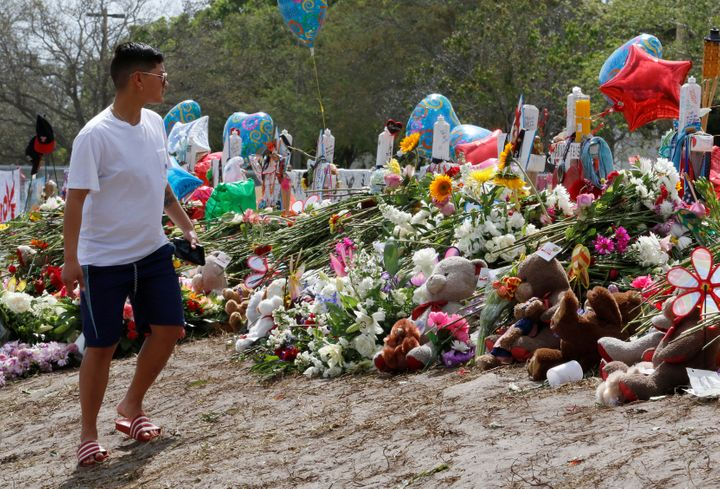 A young man views memorials on a fence surrounding Marjory Stoneman Douglas High School in Parkland, Florida, U.S., February