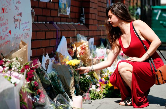 A woman lays flowers in tribute outside of Finsbury Mosque in the Finsbury Park area of north