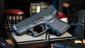 An automatic pistol handgun with a gun safe and shooting equipment.