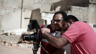 "Syrian director Humam Husari (R) and cameraman Sami al-Shami (C) operate a camera as they film a scene  in the rebel-held besieged town of Zamalka, in the Damascus suburbs, Syria September 19, 2016. REUTERS/Bassam Khabieh           SEARCH ""SYRIA FILM"" FOR THIS STORY. SEARCH ""WIDER IMAGE"" FOR ALL STORIES.    THE IMAGES SHOULD ONLY BE USED TOGETHER WITH THE STORY - NO STAND-ALONE USES."