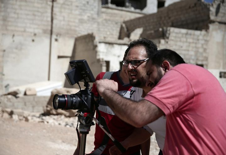 Syrian director Humam Husari, right, and cameraman Sami al-Shami, center, film a scene in the rebel-held besieged town of Zam
