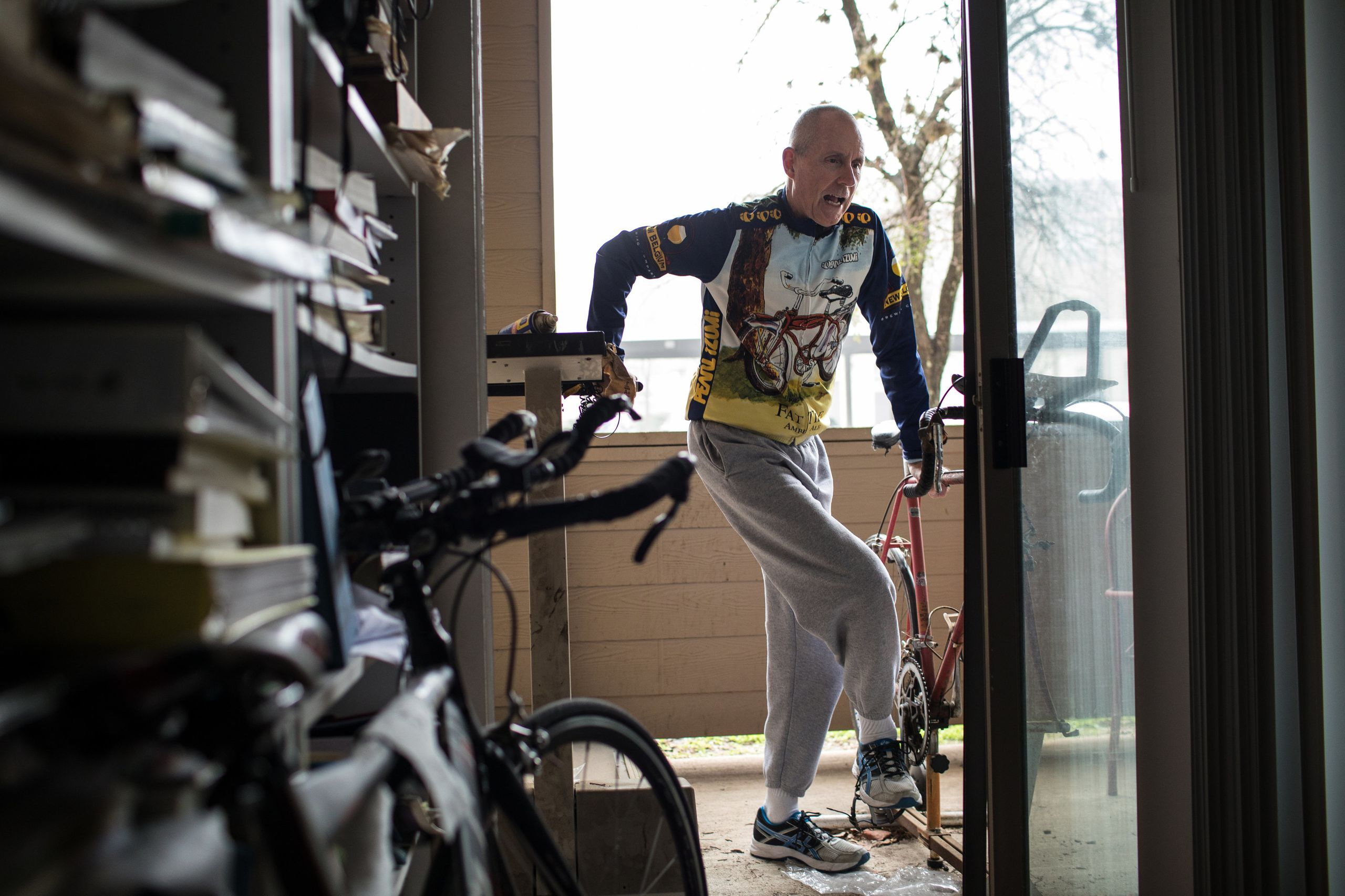 Chuck Yarling steps off his old triathlon bicycle, which he attached to a stationary bike stand on his patio outside his home