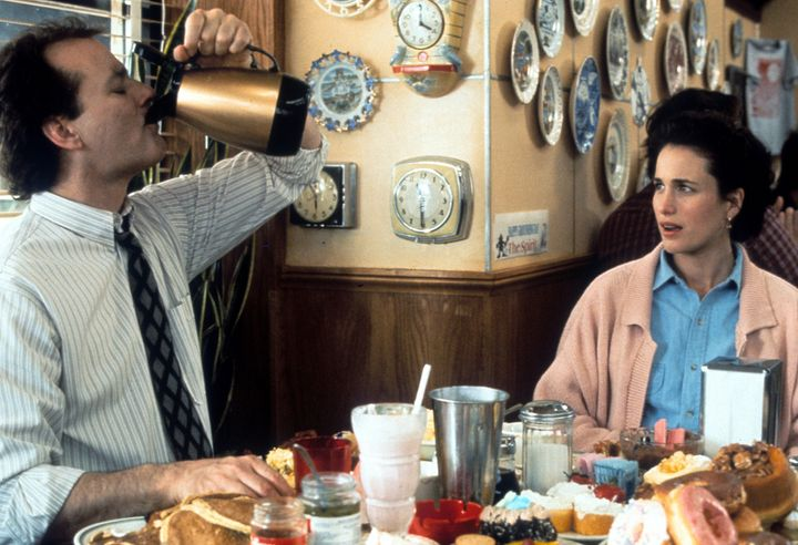 Bill Murray puts down a pitcher of coffee with Andie MacDowell in a scene from the 1993 film
