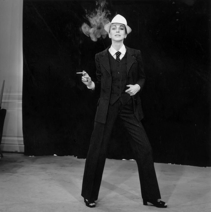 "A model wearing a pinstriped trouser suit by Yves Saint Laurent. His plainer suit for evening wear known as ""Le Smoking"" became a signature piece."