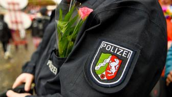 A policeman with a flower in his bag watch Revellers celebrating the street carnival at the school and quarterparade 'Schuul en Veedelzuch' on February 11, 2018 in Cologne, western Germany. / AFP PHOTO / Patrik STOLLARZ        (Photo credit should read PATRIK STOLLARZ/AFP/Getty Images)