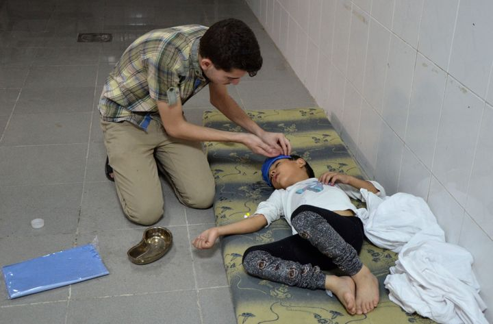 A boy is treated at a medical center in Saqba, Syria, on Aug. 21, 2013, after government forces fired rockets that released d