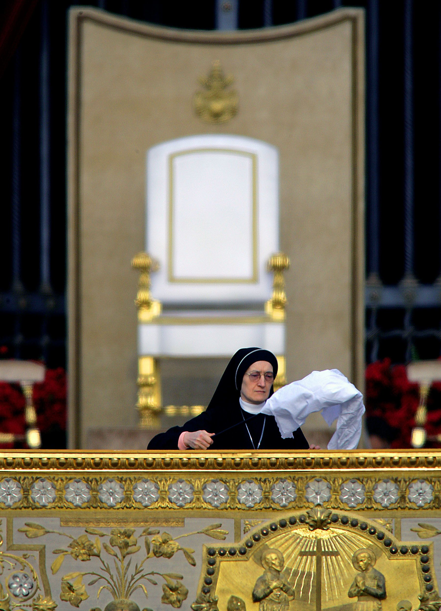 A nun cleans the main altar as the Pope's empty white chair is seen in the background before the start of the first mass of German Pope Benedict XVI at Saint Peter's Square in the Vatican April 24, 2005. REUTERS/Max Rossi  MR/JJ