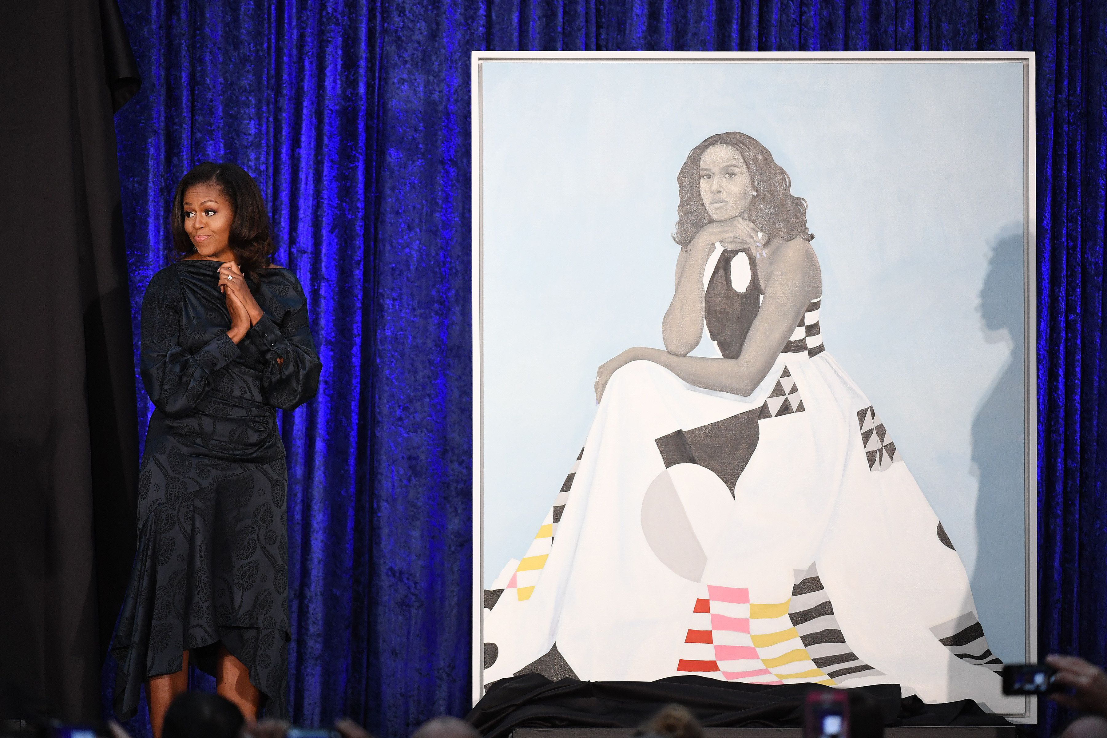 WASHINGTON, DC - FEBRUARY 12: Former First Lady Michelle Obama stands next to her portrait as she and former President Barack Obama have their portraits unveiled at the Smithsonian National Portrait Gallery on Monday February 12, 2018 in Washington, DC. The former President's portrait was painted by Kehinde Wiley while the former First Lady's portrait was painted by Amy Sherald. (Photo by Matt McClain/The Washington Post via Getty Images)