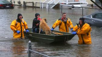 QUINCY, MA - MARCH 2: A mother and child and a dog are rescued from a flooded home on Post Island Road in the Houghs Neck section of Quincy, MA during a nor'easter storm on March 2, 2018. Quincy firefighters used boats and front-end loaders to rescue a number of residents in the area. (Photo by John Tlumacki/The Boston Globe via Getty Images)