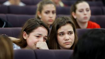 Marjory Stoneman Douglas High School student Alondra Gittelson (L) is comforted by schoolmate Bailey Feuerman after Gittleson spoke with leaders of the Florida Senate about changing laws controlling assault weapons, following last week's mass shooting on their campus, at the Capitol in Tallahassee, Florida, U.S., February 21, 2018. REUTERS/Colin Hackley
