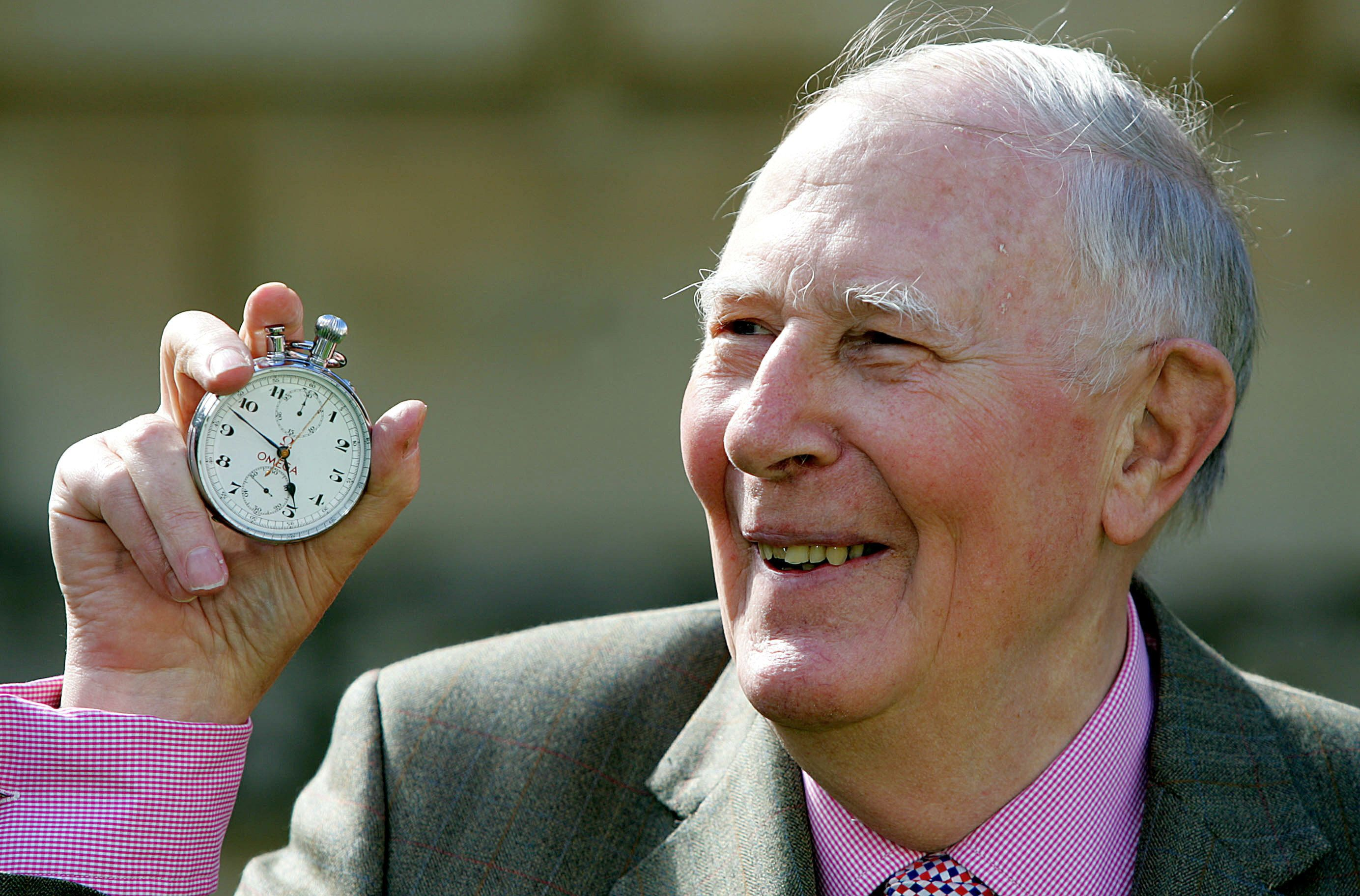 Sir Roger Bannister, who ran the first sub-four-minute mile in 1954, holds the stop watch used by [Harold Abrahams] to time the race during 50th anniversary celebrations at Pembroke College, Oxford, May 6, 2004. [Sir Roger was a 25-year-old medical student when he recorded a time of 3mins 59.4 secs for the mile on May 6 1954.]